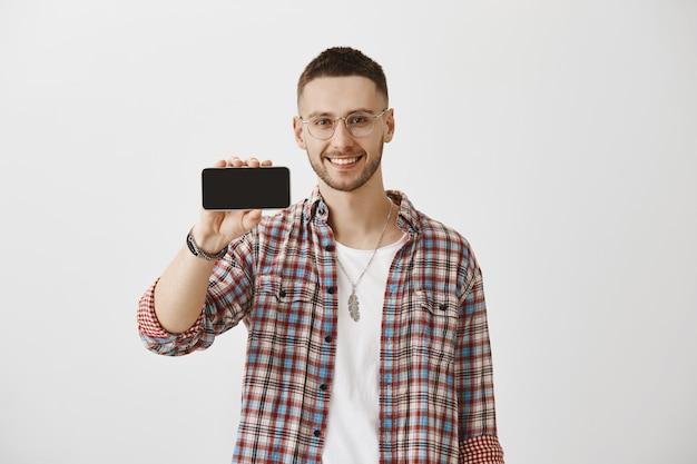 Красивый улыбающийся молодой парень в очках позирует со своим телефоном