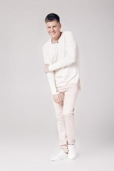 白いセーターとズボンでハンサムな笑顔の若い男