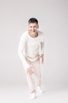 Красивый улыбающийся молодой человек в белом свитере готов бежать вперед.