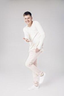 白いセーターを着たハンサムな笑顔の若い男は、孤立した彼の手を前方に伸ばします