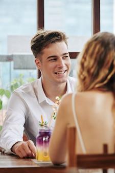 ロマンチックなデートで笑って面白い話をするハンサムな笑顔の若い男