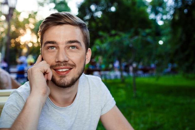 見上げる電話でオープンエアのカフェトーキンのテーブルに座っているハンサムな笑顔若い男。