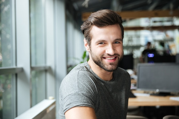 Handsome smiling young man sitting in office coworking
