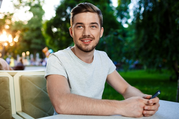 Handsome smiling young man sitting at the table in open-air cafe holding phone looking away.