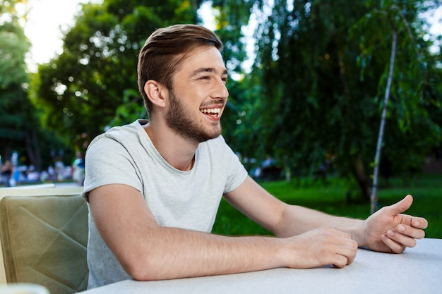 Handsome smiling young man sitting at the table in open-air cafe and looking away.