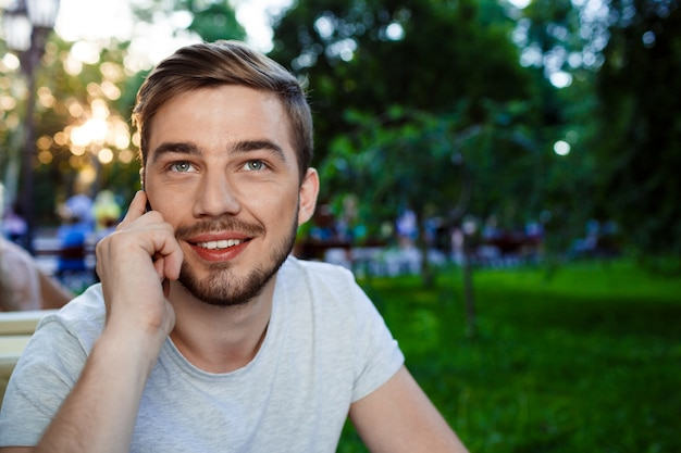 Handsome smiling young man sitting at the table in open-air cafe talkin on phone looking up.