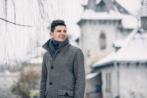 A handsome smiling young man in a warm coat and leather gloves while walking on the city