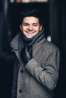 A handsome smiling young man in warm coat and leather gloves