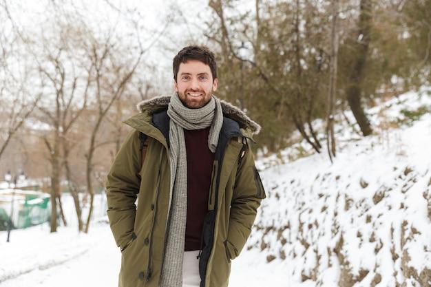Красивый улыбающийся молодой человек в зимней куртке гуляет на открытом воздухе