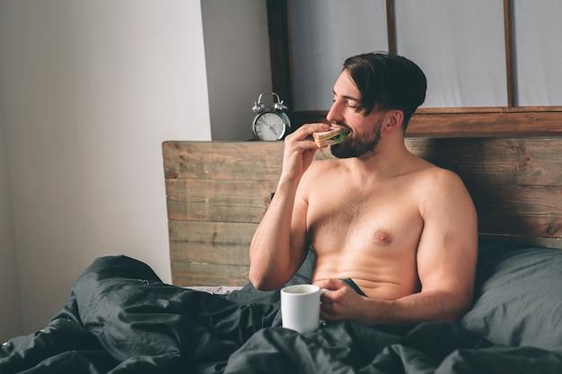 잘생긴 웃는 젊은 벌거 벗은 남자는 커피 한 잔을 들고 침대에 앉아 있는 동안 멀리 보고.