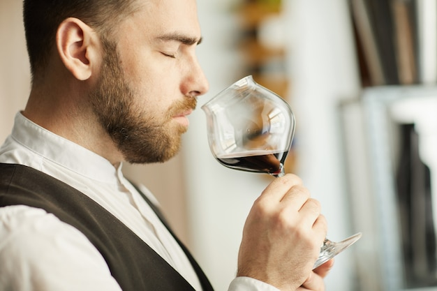 Handsome sommelier smelling wine