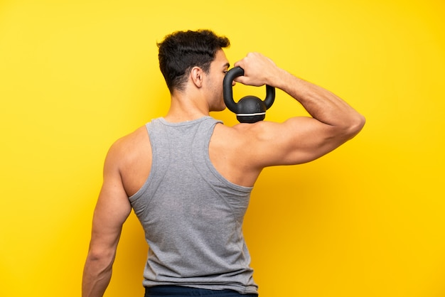 Handsome sport man over isolated background with kettlebell