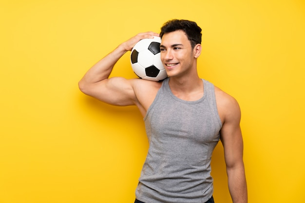 Handsome sport man over isolated background with a soccer ball