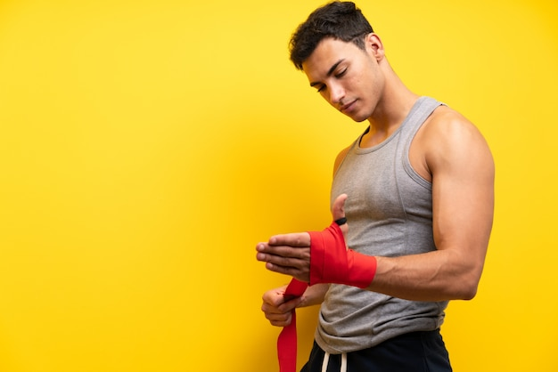 Handsome sport man over isolated in boxing bandages