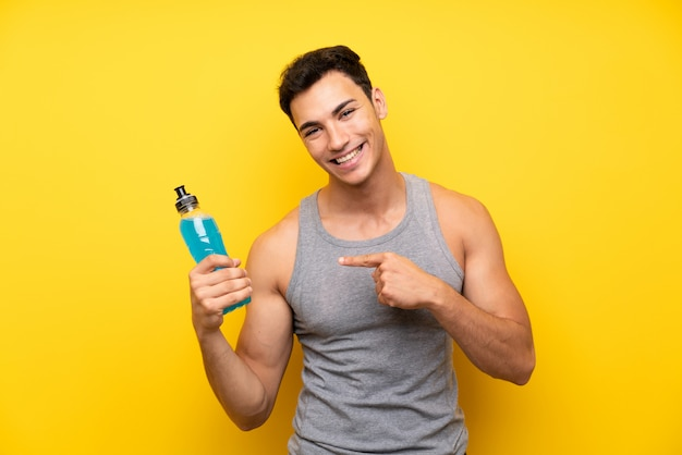 Handsome sport man over isolated wall with a bottle of soda