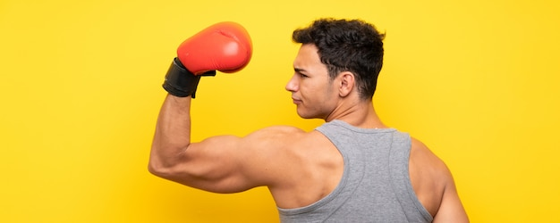 Handsome sport man over isolated wall with boxing gloves