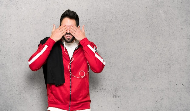 Handsome sportman covering eyes by hands. surprised to see what is ahead over textured wall