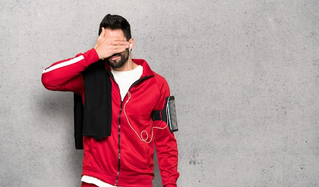 Handsome sportman covering eyes by hands. do not want to see something over textured wall