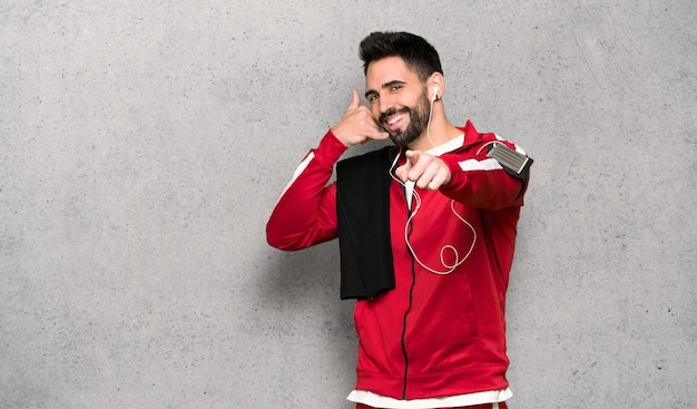 Handsome sportman making phone gesture and pointing front over textured wall