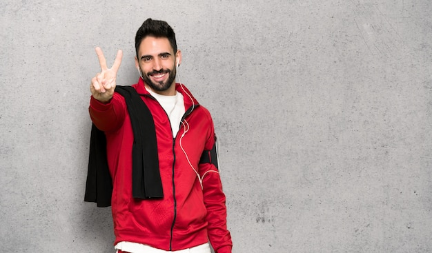 Handsome sportman smiling and showing victory sign over textured wall