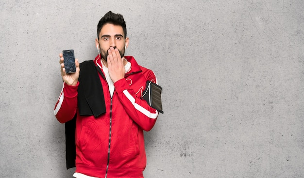 Handsome sportman with troubled holding broken smartphone over textured wall