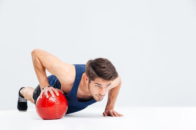 Красивый спортивный человек, работающий с фитнес-мячом, изолированным на сером фоне