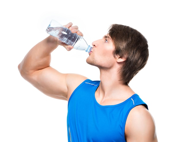 Handsome sportsman in blue shirt drinks water