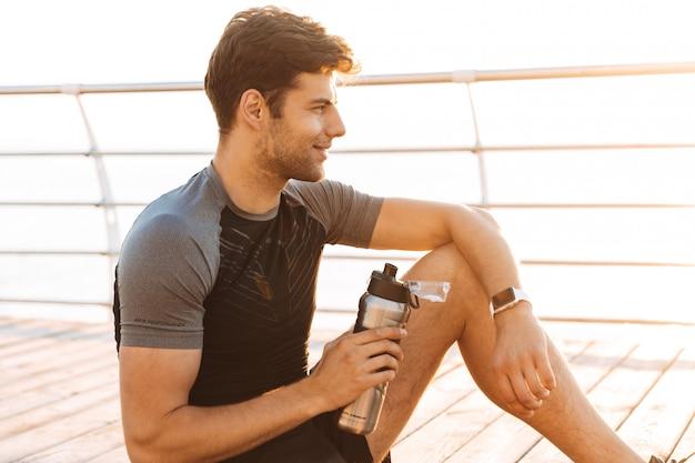 サーモスマグとマットの上に座って、朝の海辺で木製の桟橋でのトレーニングの後のトラックスーツでハンサムなスポーツマン