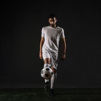 Handsome sportsman juggling ball