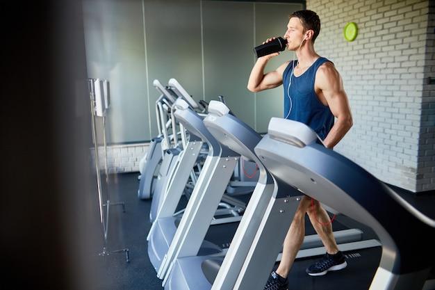 Handsome sportsman refreshing himself at gym