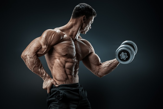 Handsome sportsman in training pumping up muscles with dumbbell strong bodybuilder with abs sixpack