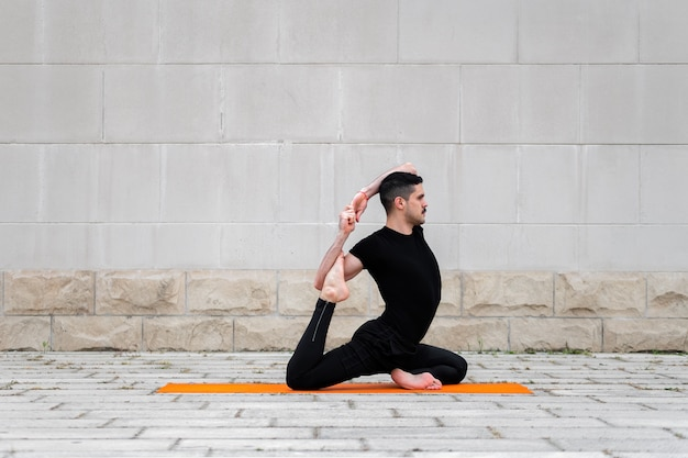 Handsome sporty latin man exercising in a city, doing yoga, fitness or pilates training, sitting in one legged king pigeon pose.