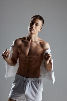 Handsome sporty man bodybuilder white towel lifestyle fitness