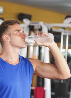 Красивый спортивный мужчина пьет минеральную воду во время тренировки в тренажерном зале