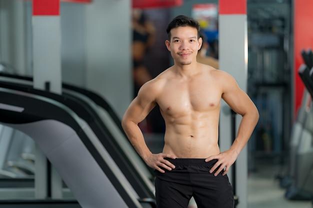 Красивый спортивный мужчина позирует в тренажерном зале
