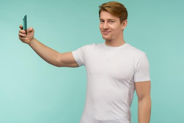 白いtシャツを着たハンサムなスポーティな赤毛の男は、青い背景のスマートフォンで自分撮りをしたり、オンラインで放送したりします。 -画像