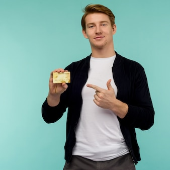 Handsome sporty red-haired guy pointing finger gold credit card on a blue background.