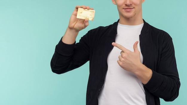 青い背景に指の金のクレジットカードを指すハンサムなスポーティな赤髪の男。 -画像