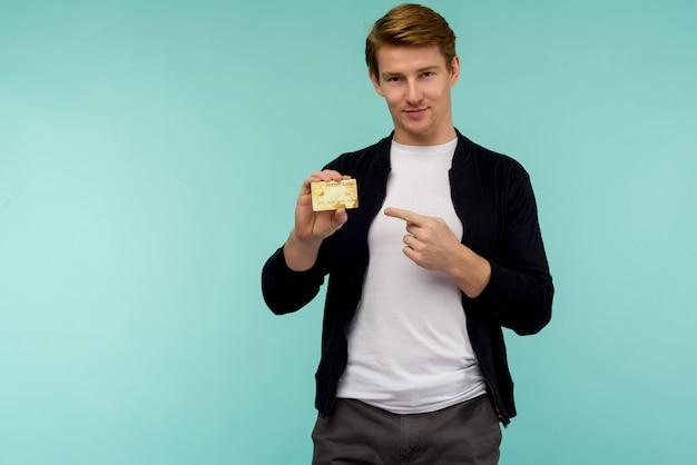 青いスペースに指の金のクレジットカードを指すハンサムなスポーティな赤い髪の男。