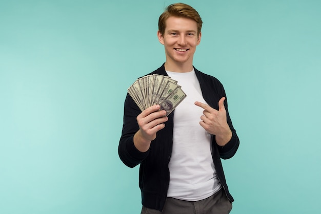 Handsome sporty red-haired guy pointing finger money on a blue background.