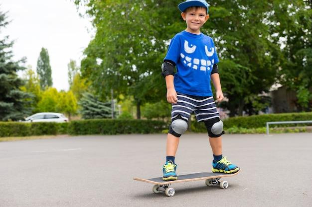 トレンディな青い服を着てスケートボードでバランスを取り、カメラに微笑んでいるハンサムなスポーティな若いスケートボーダー