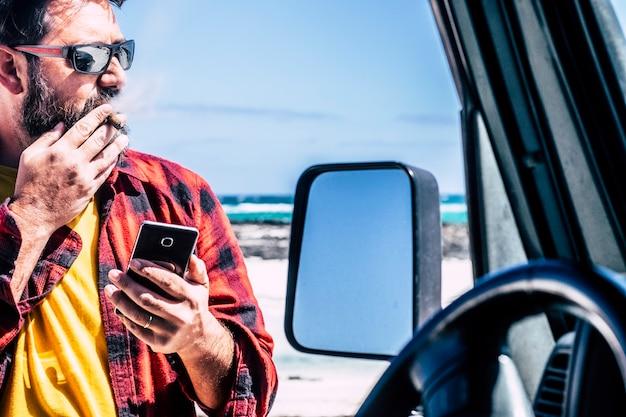 黒い車の外で葉巻を持ったハンサムな立っている男が携帯電話を使う