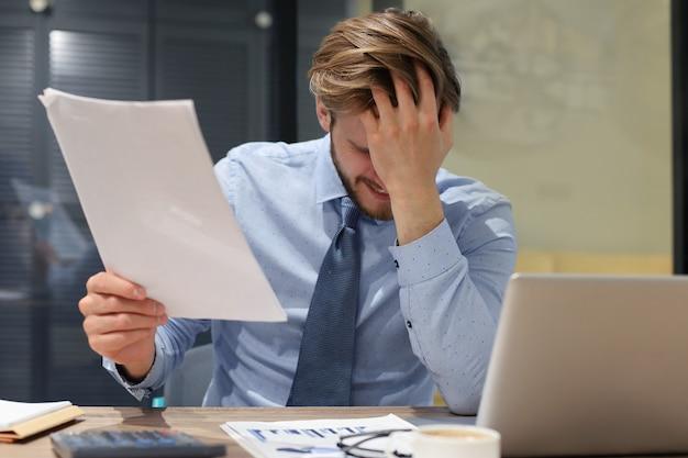 Красивый подчеркнул бизнесмен, сидя за столом в своем офисе.