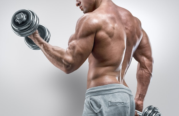 Handsome strong athletic man in training pumping up muscles with dumbbell