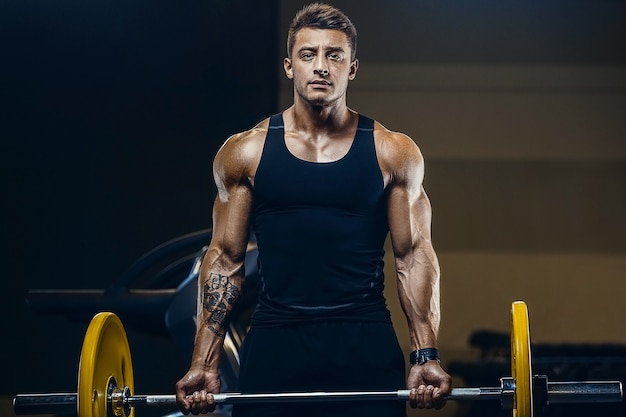 Handsome strong athletic men pumping up biceps muscles workout fitness and bodybuilding concept
