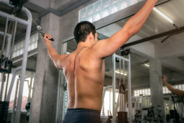 Handsome strong bodybuilder athletic asian man workout arm with cable in fitness gym.