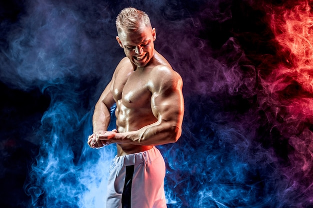 Handsome strong bodybuilder posing in  on smoke wall