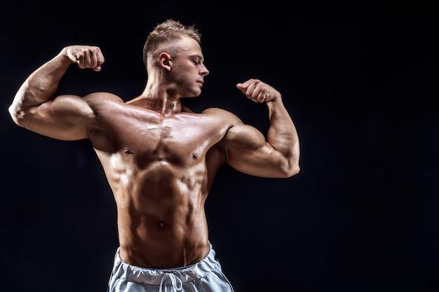 Handsome strong bodybuilder posing in studio on black