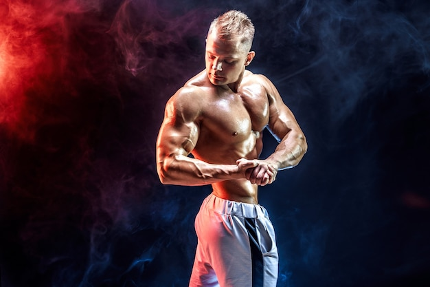 Handsome strong bodybuilder posing in studio on colored smoke