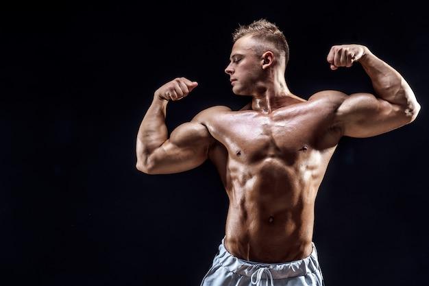 Handsome strong bodybuilder posing in